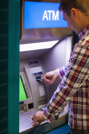 withdrawing: Brunette student withdrawing cash at an ATM Stock Photo