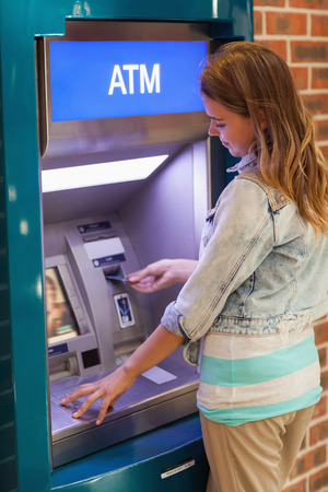Pretty happy student withdrawing cash at an ATM Stock Photo