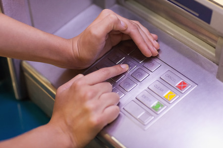 Close up of hand entering pin at an ATM photo