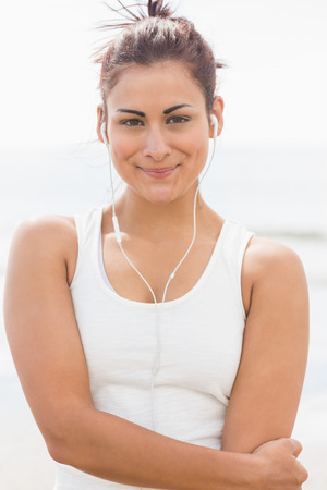 Beautiful smiling woman listening to music through earphones at beach photo