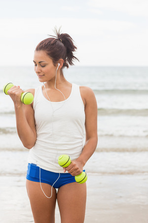 Focused smiling woman lifting dumbbells on the beach while listening to music photo