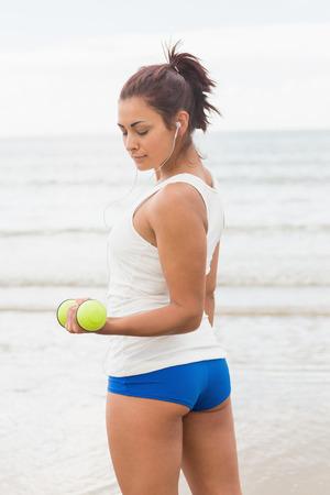 Lovely sporty woman lifting concentrated dumbbells on the beach photo