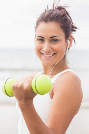 Cute smiling woman lifting dumbbells on the beach smiling at camera photo