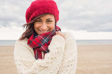Close up of a cute smiling young woman in stylish warm clothing on the beach photo