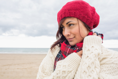 Close up of a young woman in knitted hat and pullover looking away on the beach photo