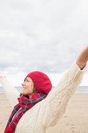 Young woman in warm clothing stretching her arms on the beach photo