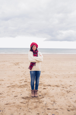 Full length portrait of a pretty young woman in stylish warm clothing at the beach photo