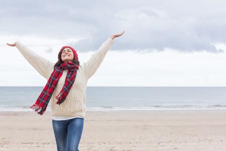 robo: Mujer joven en ropa de abrigo que estira sus brazos en la playa