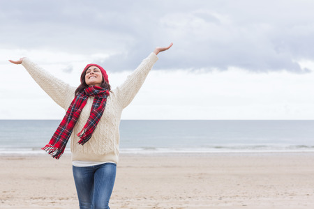 beach wear: Young woman in warm clothing stretching her arms on the beach