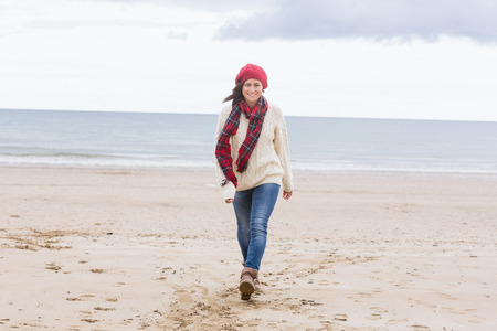Full length of a pretty young woman in stylish warm wear walking at the beach photo