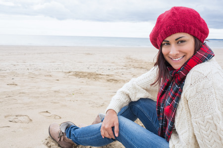 Portrait of a smiling young woman in stylish warm clothing sitting on the beach photo