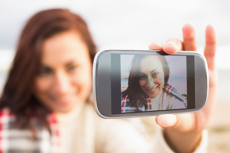 Smiling blurred young woman self photographing with a smartphone on the beach photo