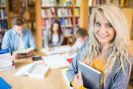 Portrait of a smiling female student with others in background in the college library photo
