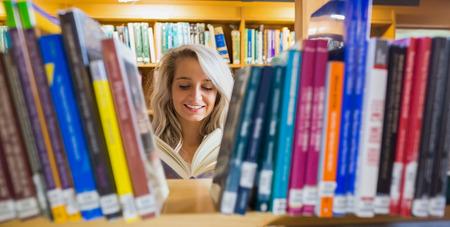 Sourire jeune étudiante de lecture de livres au milieu des étagères de la bibliothèque de l'université