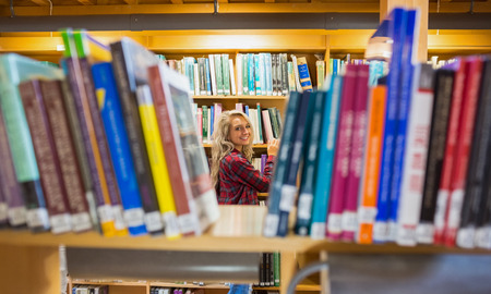 Portrait of a smiling young female amid bookshelves in the college library photo