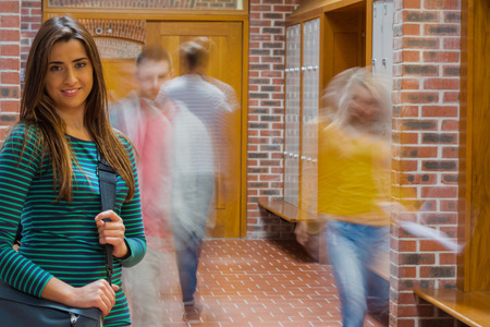 Portrait of a smiling girl with blurred college students walking through corridor photo