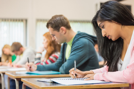 indian student: Side view of a group of young students writing notes in the classroom Stock Photo