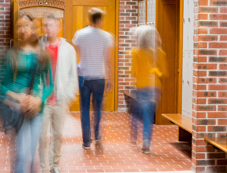 Group of blurred college students walking through corridor photo