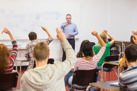 alumno estudiando: Vista posterior de los estudiantes con las manos levantadas con un profesor en el aula Foto de archivo