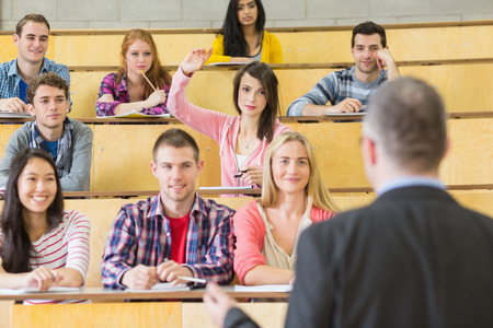 Rear view of an elegant teacher with students sitting at the college lecture hall photo