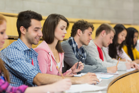 casuals: Side view of students writing notes in a row at the college lecture hall