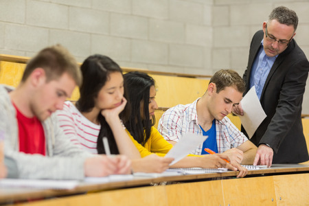 casuals: Elegant teacher with students writing notes at the college lecture hall Stock Photo