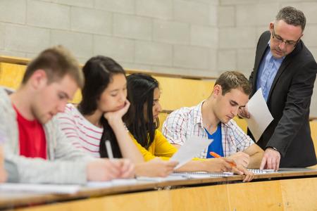 maestra enseñando: Profesor elegante con estudiantes escribiendo notas en el aula magna de la universidad