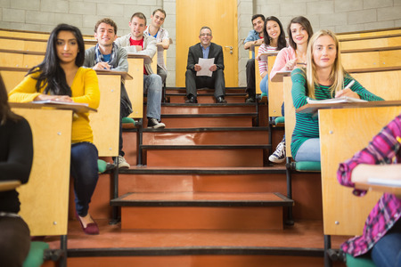 casuals: Portrait of an elegant teacher with students sitting at the college lecture hall