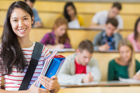 casuals: Portrait of a smiling female with students sitting at the college lecture hall