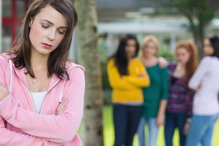 peer to peer: Mujer estudiante siendo intimidado por otro grupo de estudiantes Foto de archivo