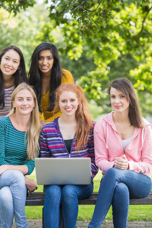 Group portrait of young college girls with laptop in the park photo
