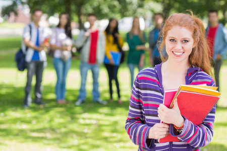 college campus: Portrait of college girl holding books with blurred students standing in the park