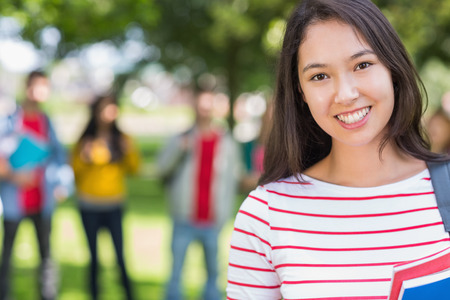 Close-up portrait of college girl with blurred students standing in the park photo