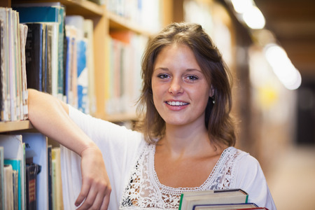 Close up portrait of a smiling female student in the library photo