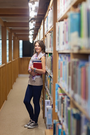 Portrait of a smiling female student standing against bookshelf in the library photo