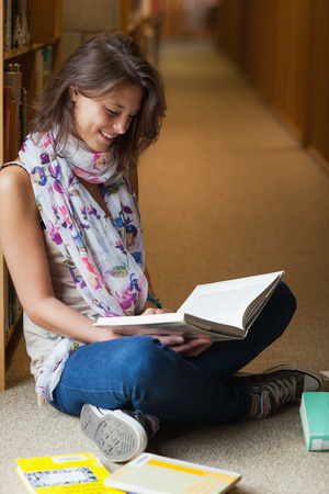 Full length of a female student sitting and reading a book in the library photo