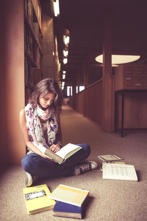 Full length of a female student sitting and reading a book in the library aisle photo