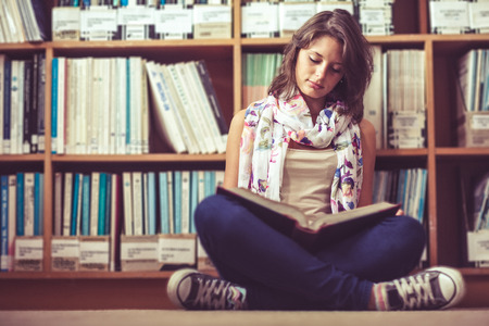 Full length of a female student sitting against bookshelf and reading a book on the library floor photo