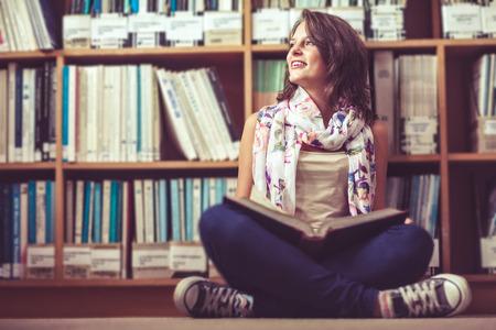 akademický: Promyšlený žena student sedí na polici s knihou na podlaze knihovny