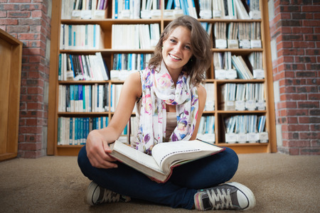 Full length of a happy female student sitting against bookshelf with a book on the library floor photo