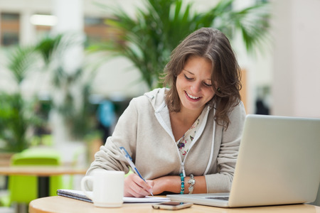adult writing: Smiling female student doing homework by laptop at cafeteria table