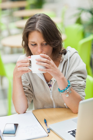 Serious female student drinking coffee while using laptop at cafeteria table photo