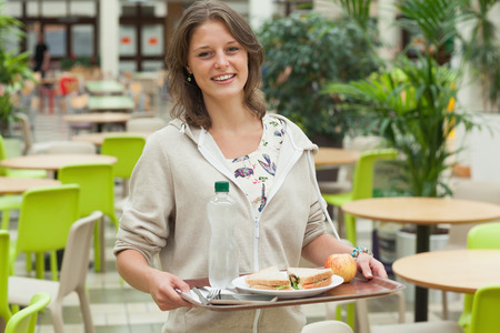 Portrait of a female student carrying food tray in the cafeteria photo