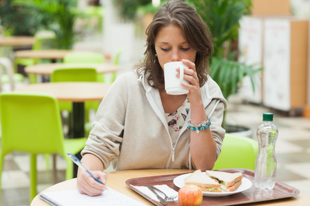 school cafeteria: Female student doing homework while having breakfast in the cafeteria