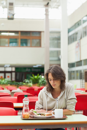 cafeteria tray: Alone and sad female student sitting in the cafeteria with food tray