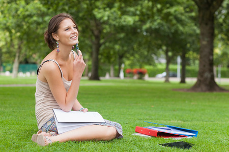 Thoughtful female student with books sitting at the park photo