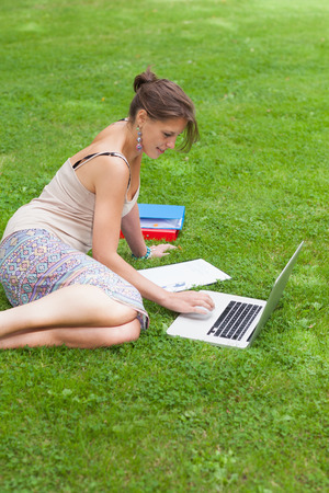 Side view of a female student using laptop with books at the park photo
