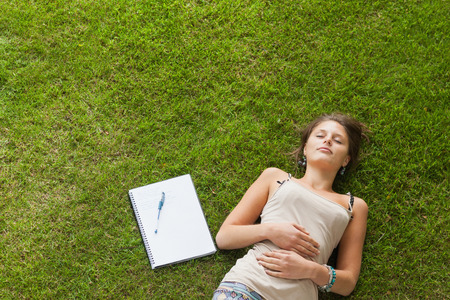 High angle view of a female student resting on grass at the park photo