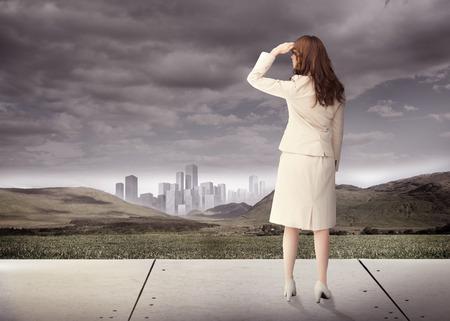 mujer mirando el horizonte: Vista trasera de una morena de negocios en frente de cielo nublado
