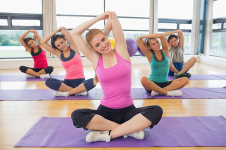 Portrait of fitness class and instructor sitting on yoga mats and stretching hands photo